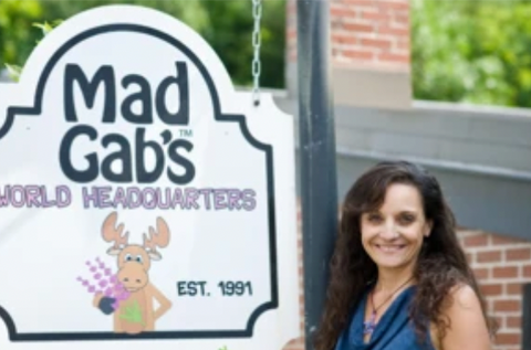 Mad Gab's owner, Gabrielle Melchionda, is standing in front of the Mad Gab's World Headquarters sign in Yarmouth, Maine