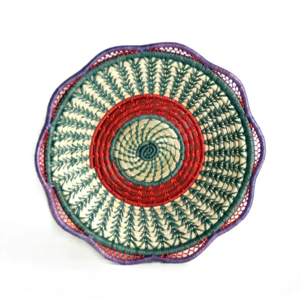 Josefina basket is a fair trade delicately handwoven basket made of native grass and pine needles with colorful raffia accents and a scalloped rim, created and designed by the women of Mayan Hands El Triunfo cooperative.