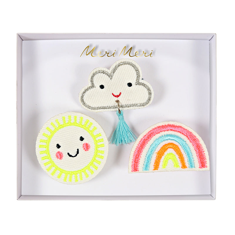 Three felt brooches embroidered with a sun, a cloud and a rainbow