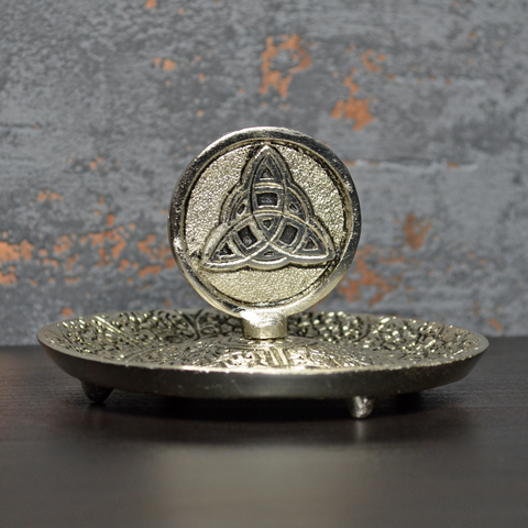 Silver coloured metal incense plate featuring a celtic symbol