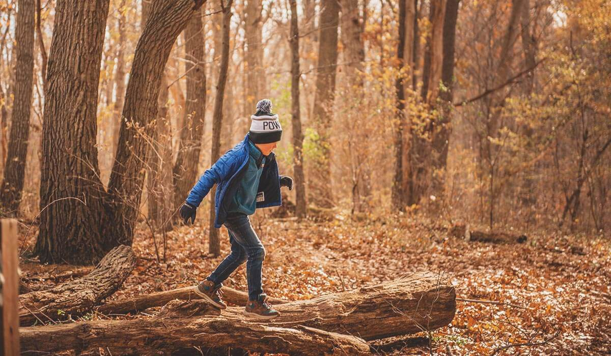 young boy walking on log in fall