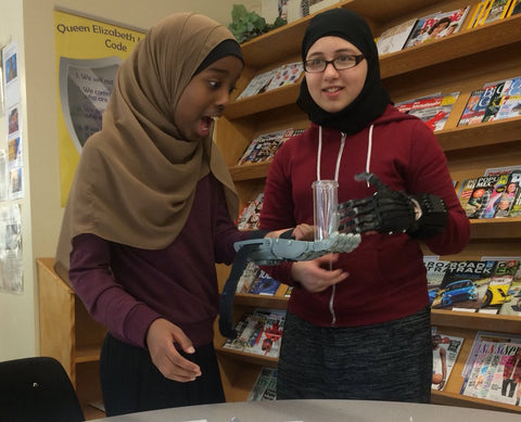 Excited students testing their 3D printed prosthetic hand