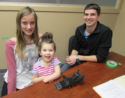 Student working to 3D print a prosthetic hand for a small girl