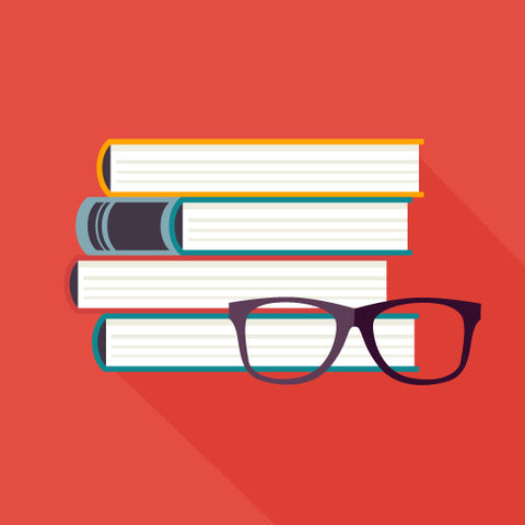 A stack of books with a pair of glasses in front on a red background.