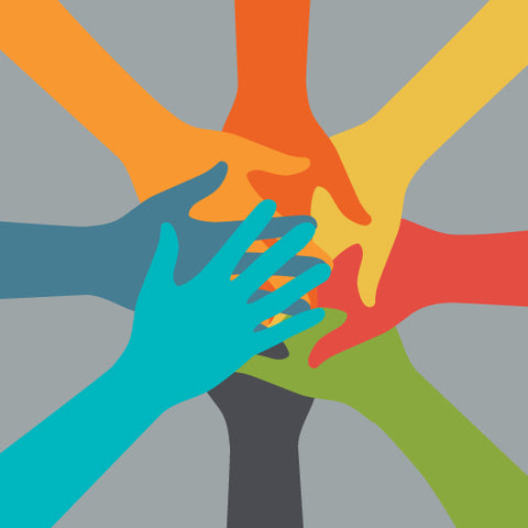 Multi-colored hands on top of each other on a grey background.