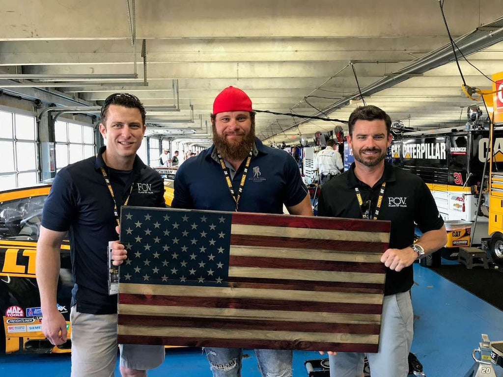 Joe and Brian giving wooden American flag to combat wounded veteran