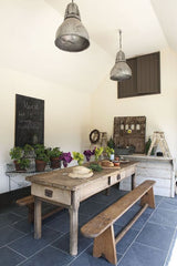 Old bakers table set as dining table in fresh clean modern kitchen with old benchs