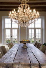 Chunky old wooden dining table with wide rustic beams set in a grand and glamorous room beneath a huge sparkling chandelier