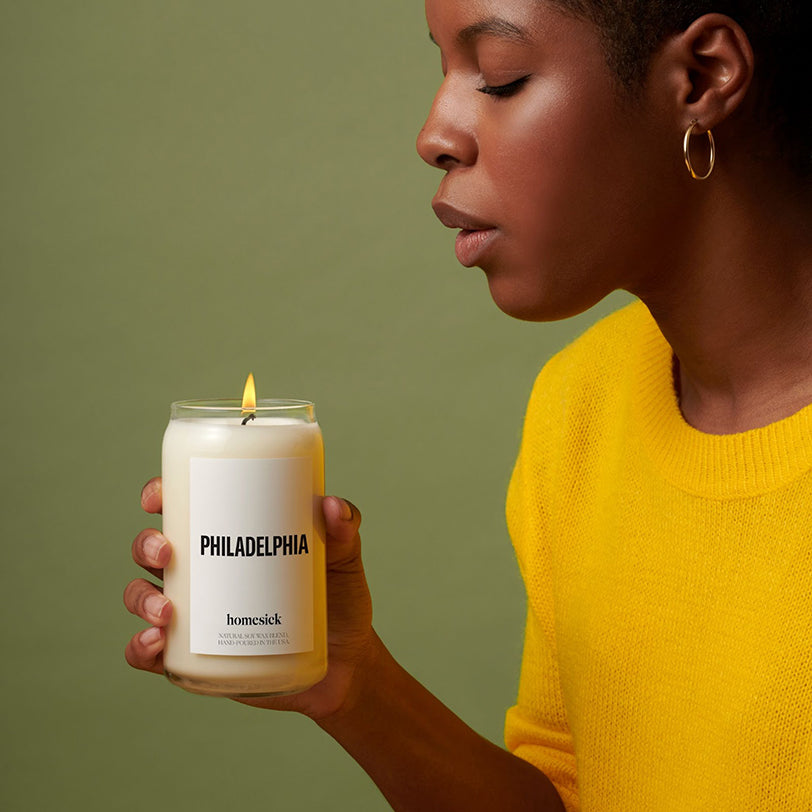 a woman about to blow out a homesick Philadelphia candle that shes holding