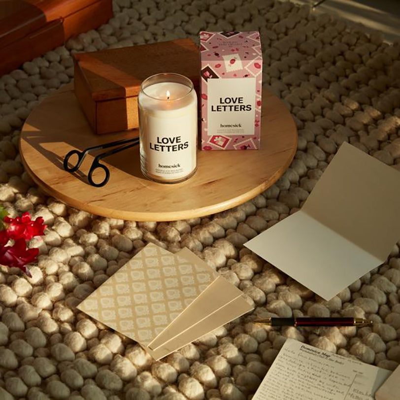 a Homesick love letters candle on a wooden saucer with a candle care kit