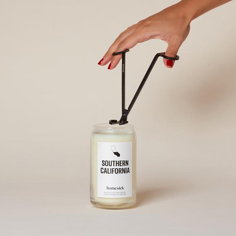 a person trimming the wick of a homesick southern california candle
