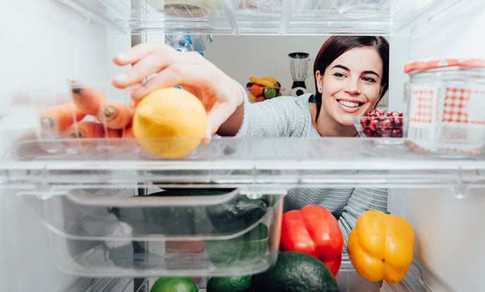woman looking through fridge