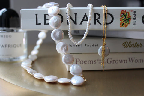 3 varied pearl necklaces hanging over a stack of books on a gold side table