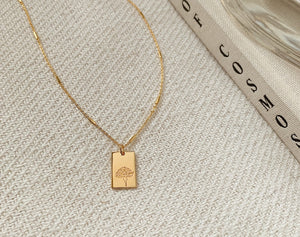 A delicate gold necklaces with a tile pendant which has a flower engraved on it, placed on a beige rug next to a beige coffee table book