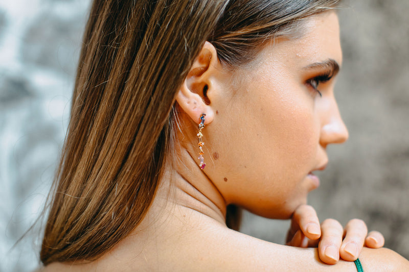 Styled image of side view of brunette woman wearing our Rainbow Drop earrings.