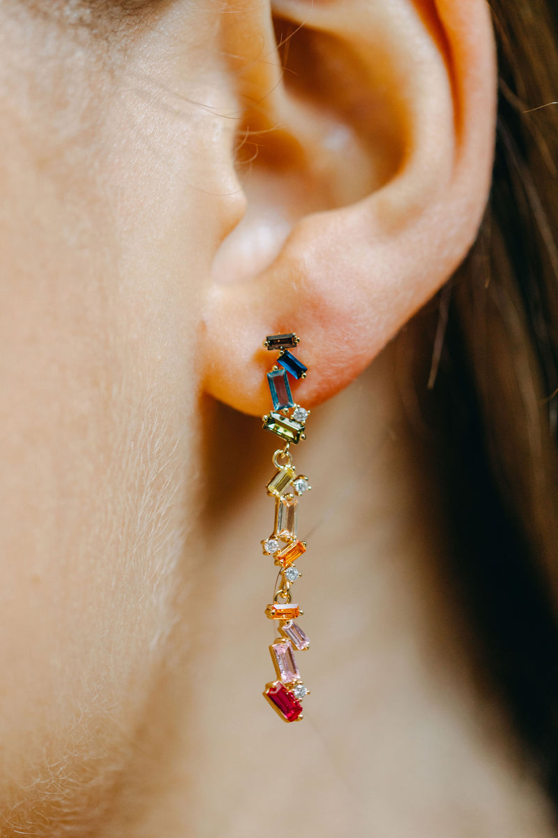 Styled image of our Rainbow Drop earrings being worn on an ear.