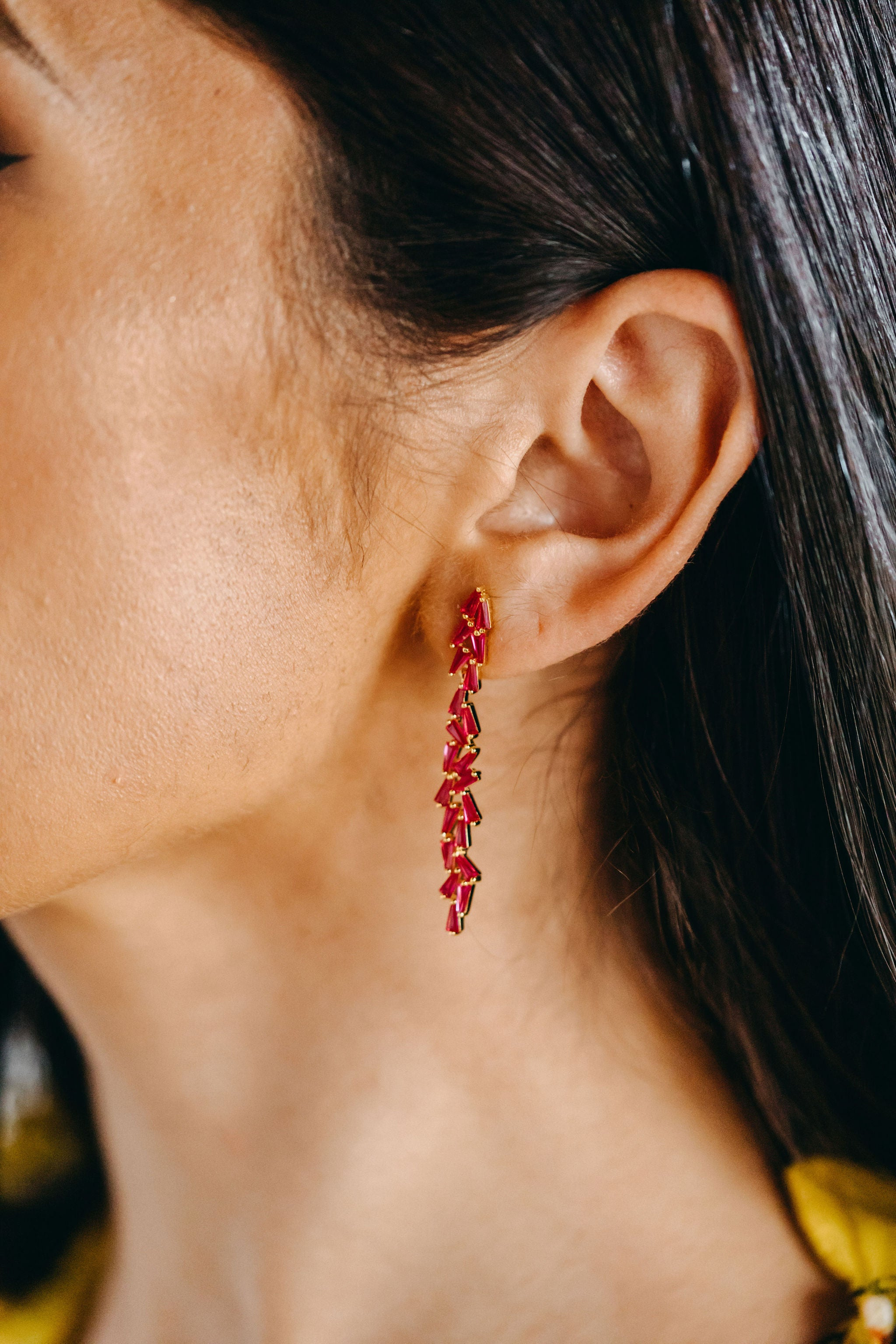 Styled image of our Aurora earrings being worn on the ear of a brunette woman.