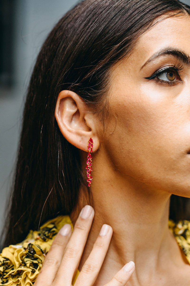 Styled image of our aurora earrings being worn by a brunette woman as she gazes into the distance.