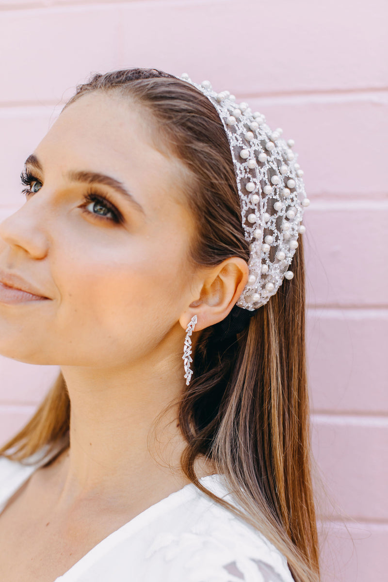 Styled image of our aurora earrings being worn by a brunette woman wearing a silver headband as she looks into the distance.