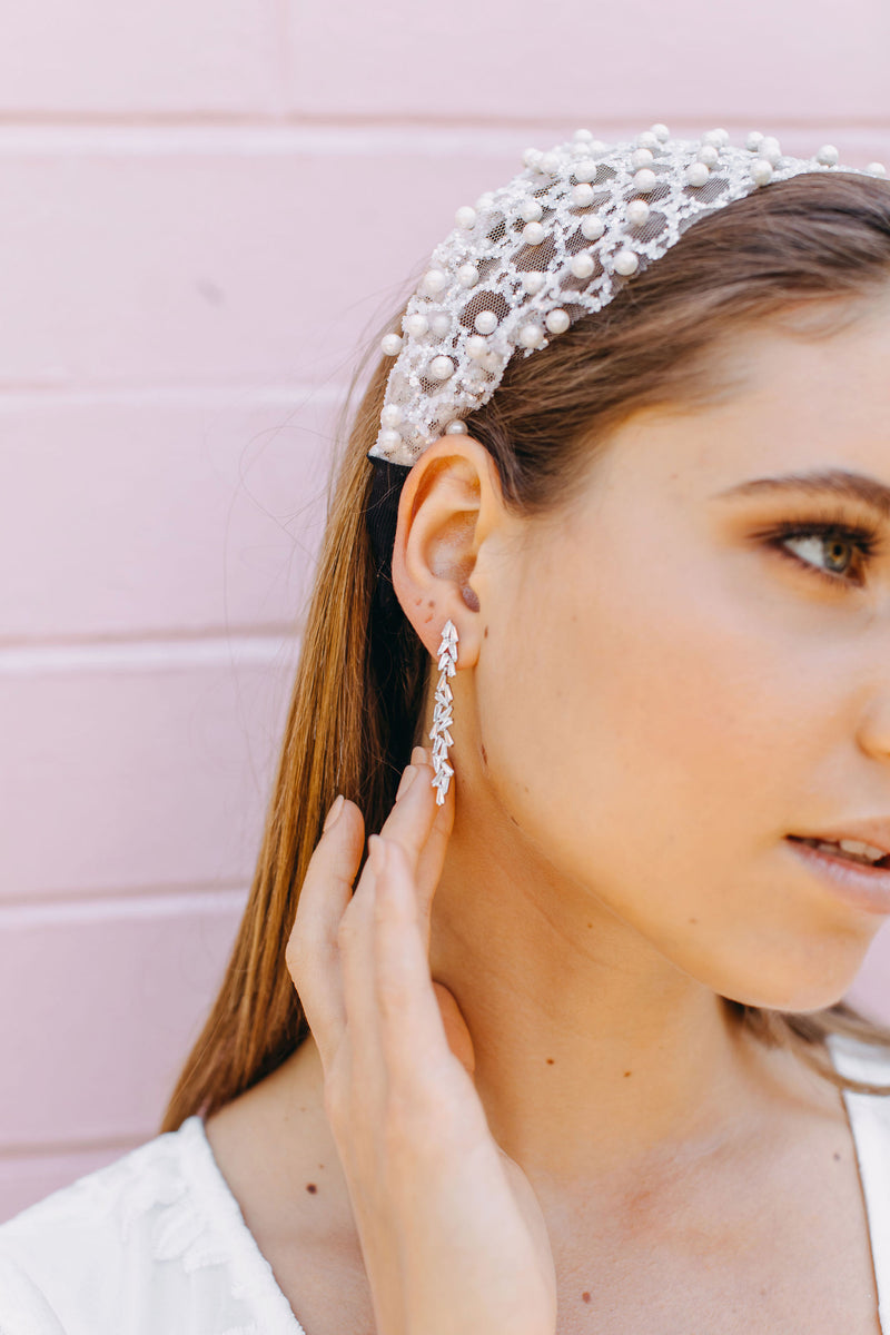 Styled image of our aurora earrings being worn by a brunette woman wearing a silver headband.