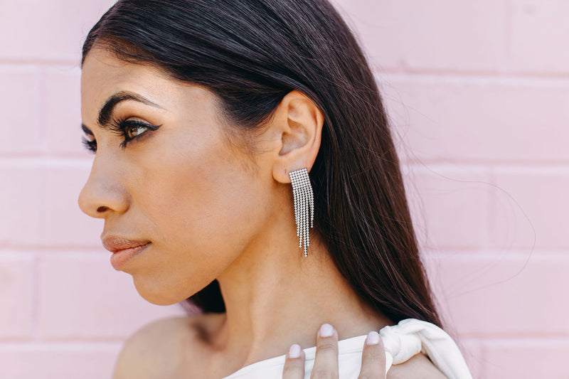 Brunette woman looking into the distance, wearing our Equinox earrings.