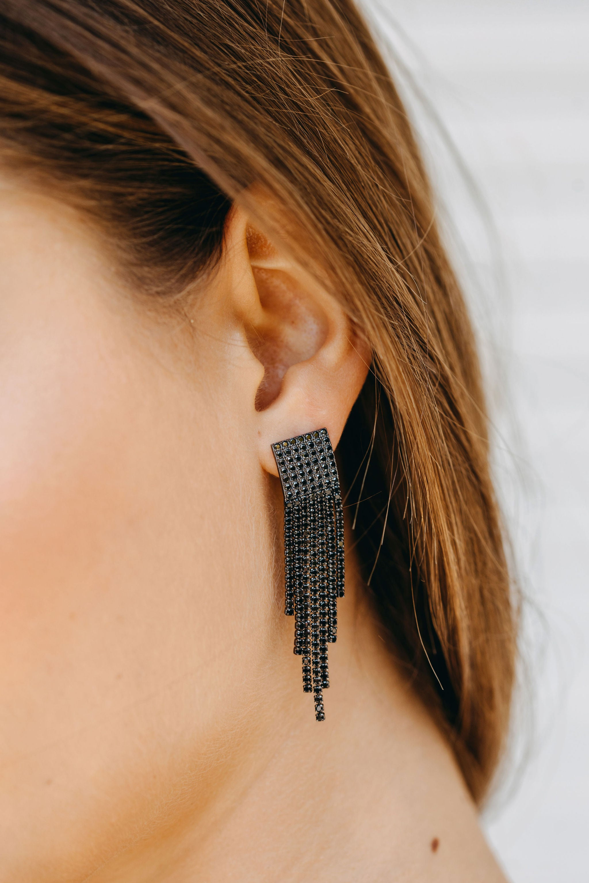 Styled image of our Equinox earrings being worn by brunette woman.
