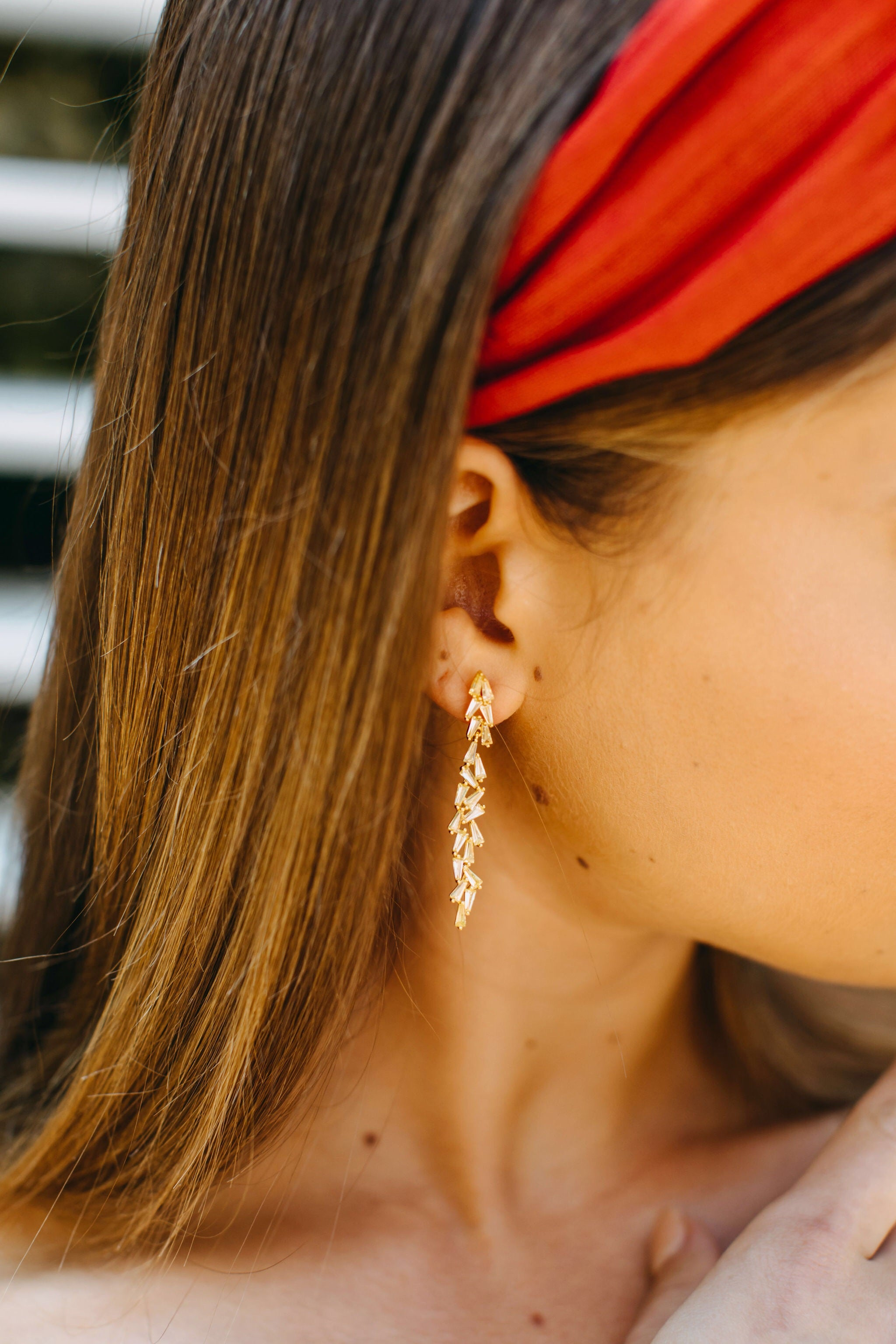 Styled image of our aurora earrings from the side view, worn on the ear of a brunette woman wearing a red headband.