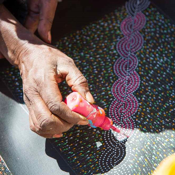 Aboriginal artist Elizabeth Kunoth Kngwarreye paints flowers with bottle