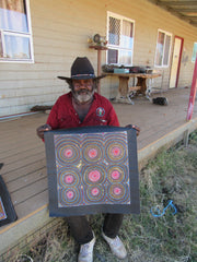 George Petyarre holding square dot painting