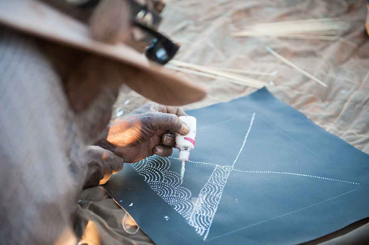 Aboriginal artist uses ink bottle to paint dots on canvas