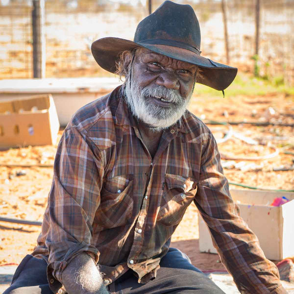 Dinny Kunoth wearing a plaid shirt and black cowboy hat, sitting facing forward with a big smile