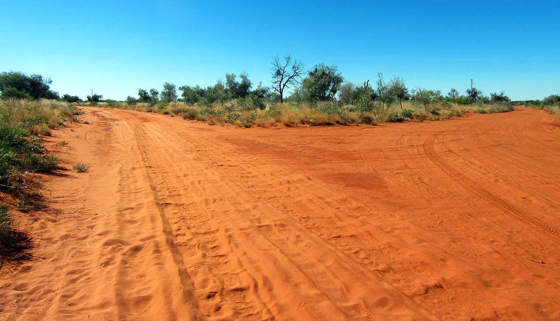 Red dirt road junction at Utopia in Central Australia. Photo by Utopia Lane Gallery