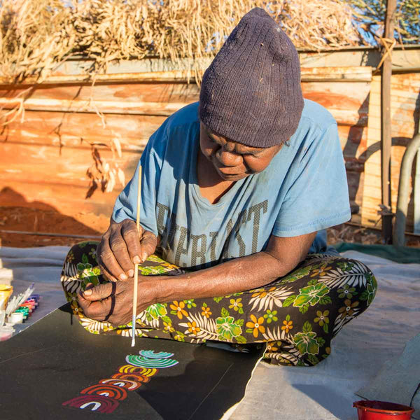 Josie Kunoth Petyarre wearing blue t-shirt and beannie, sitting over a small canvas in front of a corrugated tin wind break, painting with a brush.