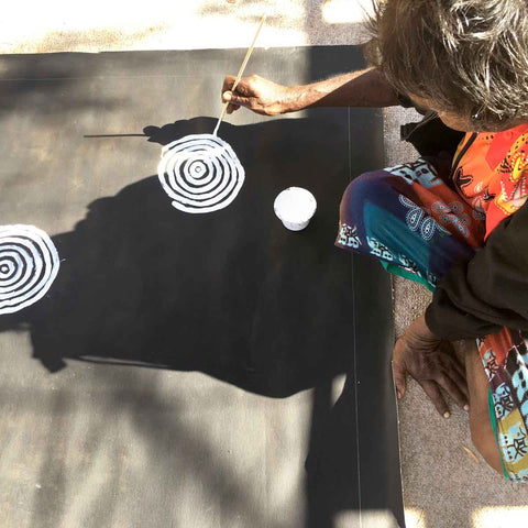 Aboriginal artist Betty Mbitjana leans over canvas to paint concentric circles