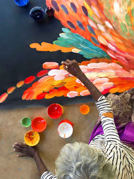 Birds eye view of Gloria Petyarre sitting on porch painting a large orange leaves painting
