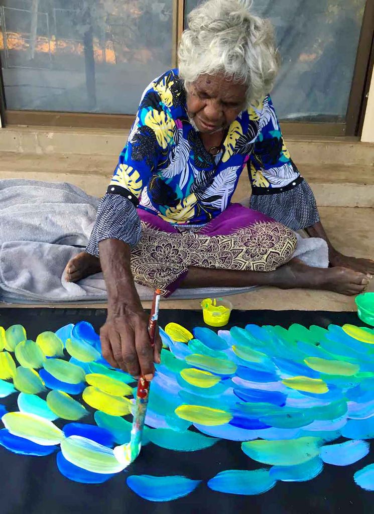 Gloria Petyarre sitting on concrete porch painting a large blue and green canvas.
