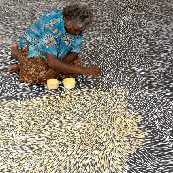 Gloria Petyarre sits in the centre of a giant 18'x12' canvas with one layer of small leaves complete.