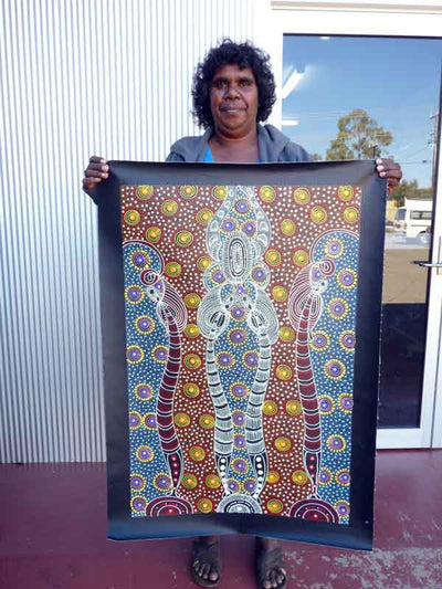 Colleen Wallace Nungari holding a Dreamtime Sisters painting