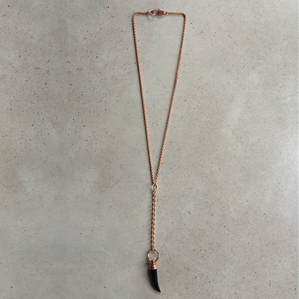 long rose gold necklace with black glass pendant