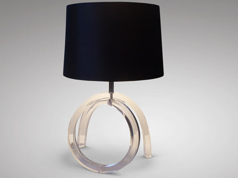 A distinctive 1970s Lucite table lamp with translucent curved lines elegantly contrasting with a powerful, deep black shade.