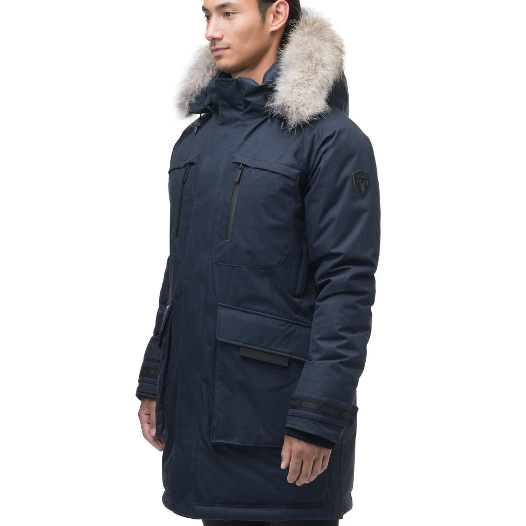 Men's thigh length down-filled parka with removable hood and removable coyote fur trim in Navy