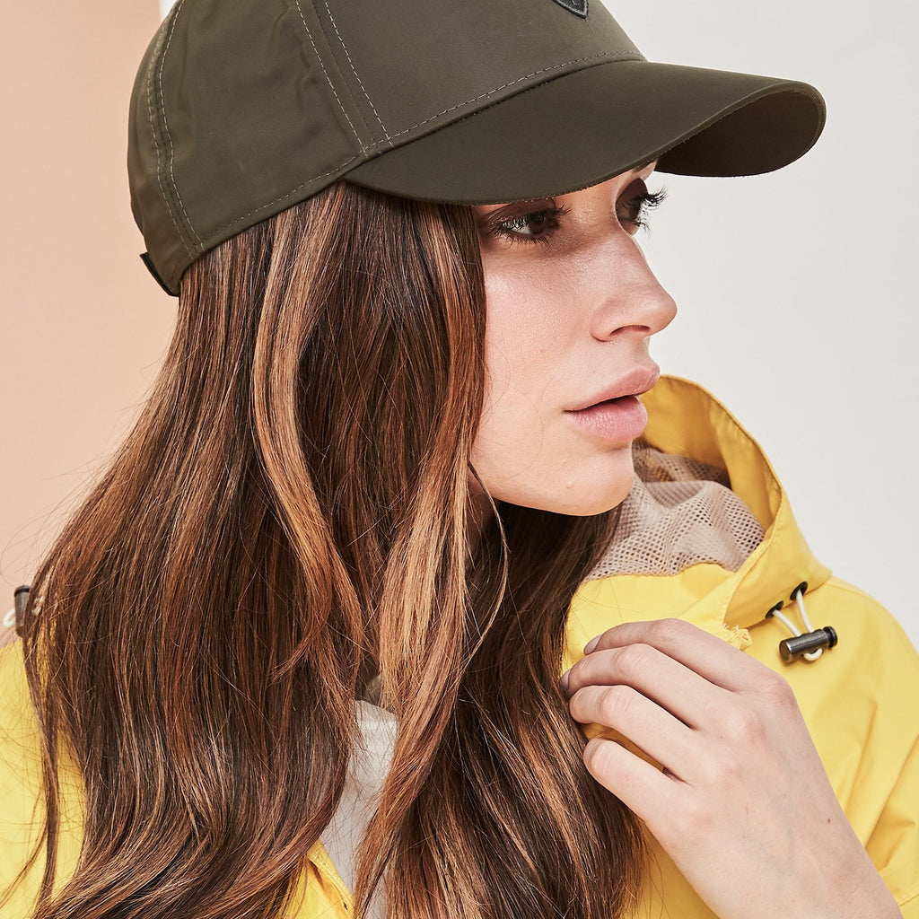 Model wearing five panel baseball hat with adjustable back in Fatigue