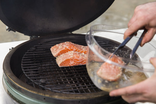 placing the salmon over Fogo All Natural Lump Charcoal