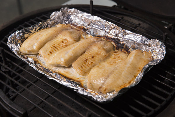 tilapia on a foil bed over Fogo All Natural Lump Charcoal