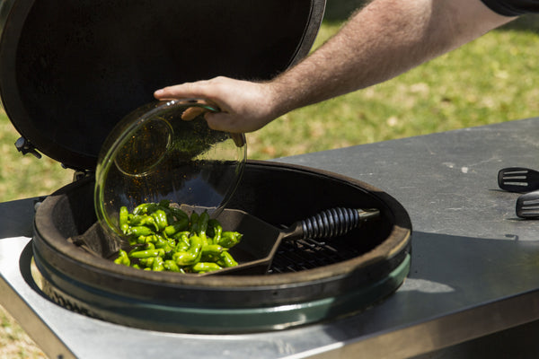 placing the peppers on the hot pan over Fogo All Natural Lump Charcoal