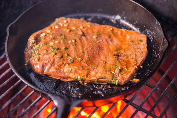 adding the steak in the cast iron skillet