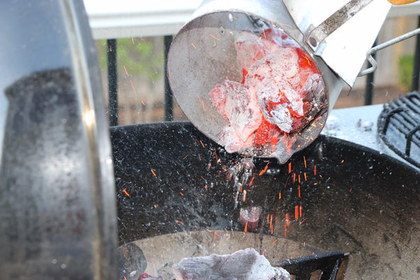 Pouring Fogo Premium Lump Charcoal into the grill