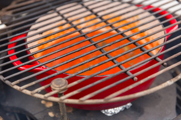 preparing the grill with the dutch oven in between the grate and the indirect heat plates
