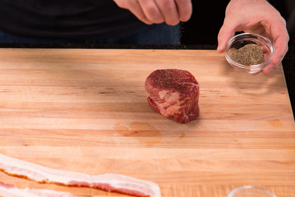 preparing the steak with salt and pepper