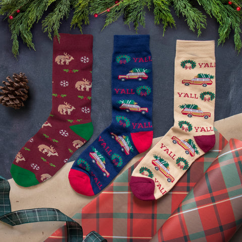 Three Y'alliday crew socks, Reindeer Humping in burgundy, Y'all with wreaths in navy, and Y'all with wreaths in tan. Styled in flat lay on brown plaid with fir trim and pinecone